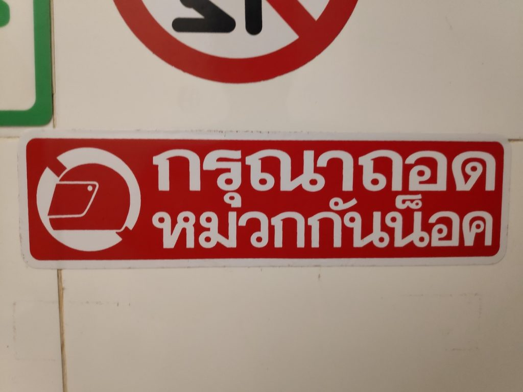 sign please remove helmet in thai